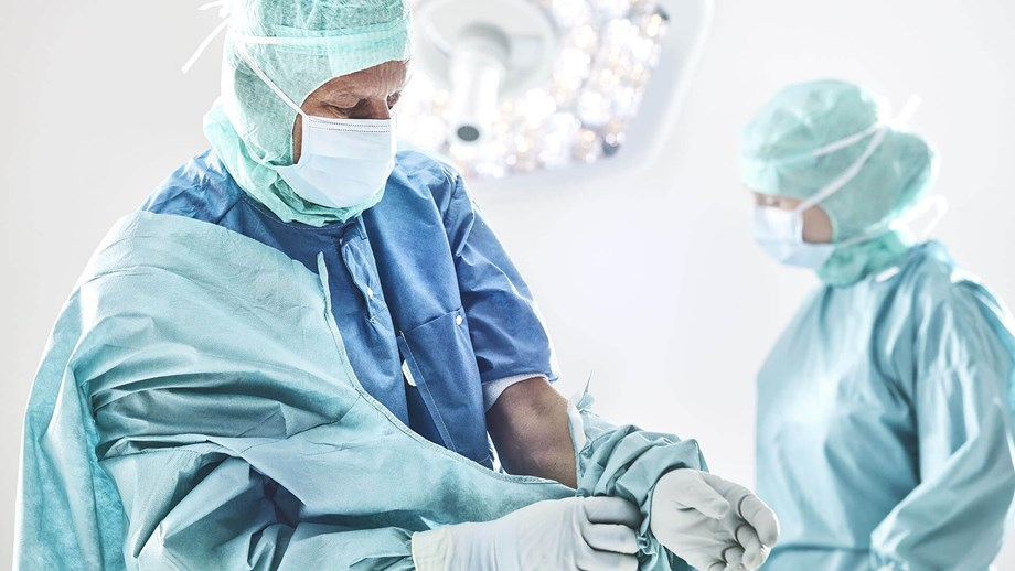 Surgeon donning a gown before surgery